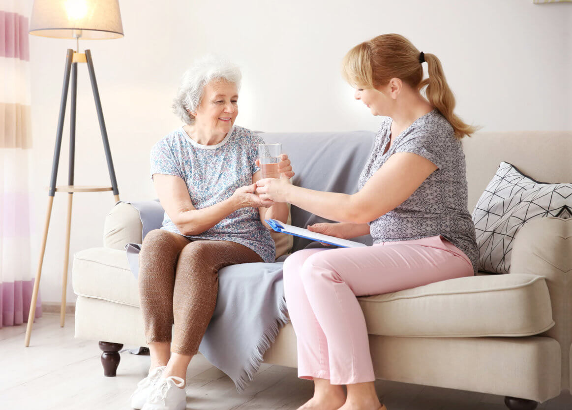 caregiver offering water to senior woman