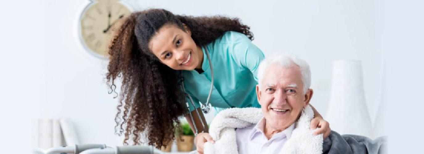 female caregiver and senior man smiling indoor